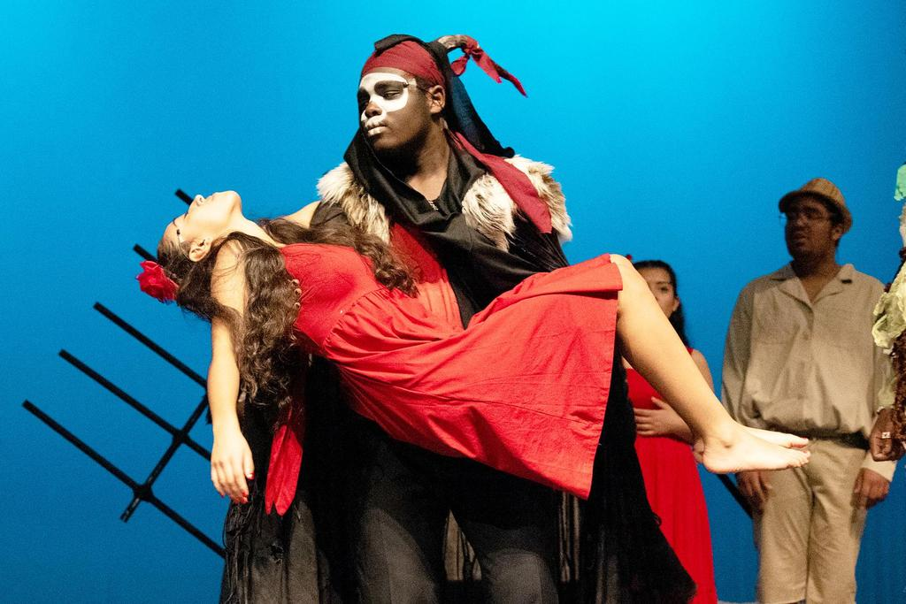 Marck- Hens Jules, who plays Papa Ge, Demon of Death, lifts and holds Jhalyshka Feliciano, who plays Ti Moune
