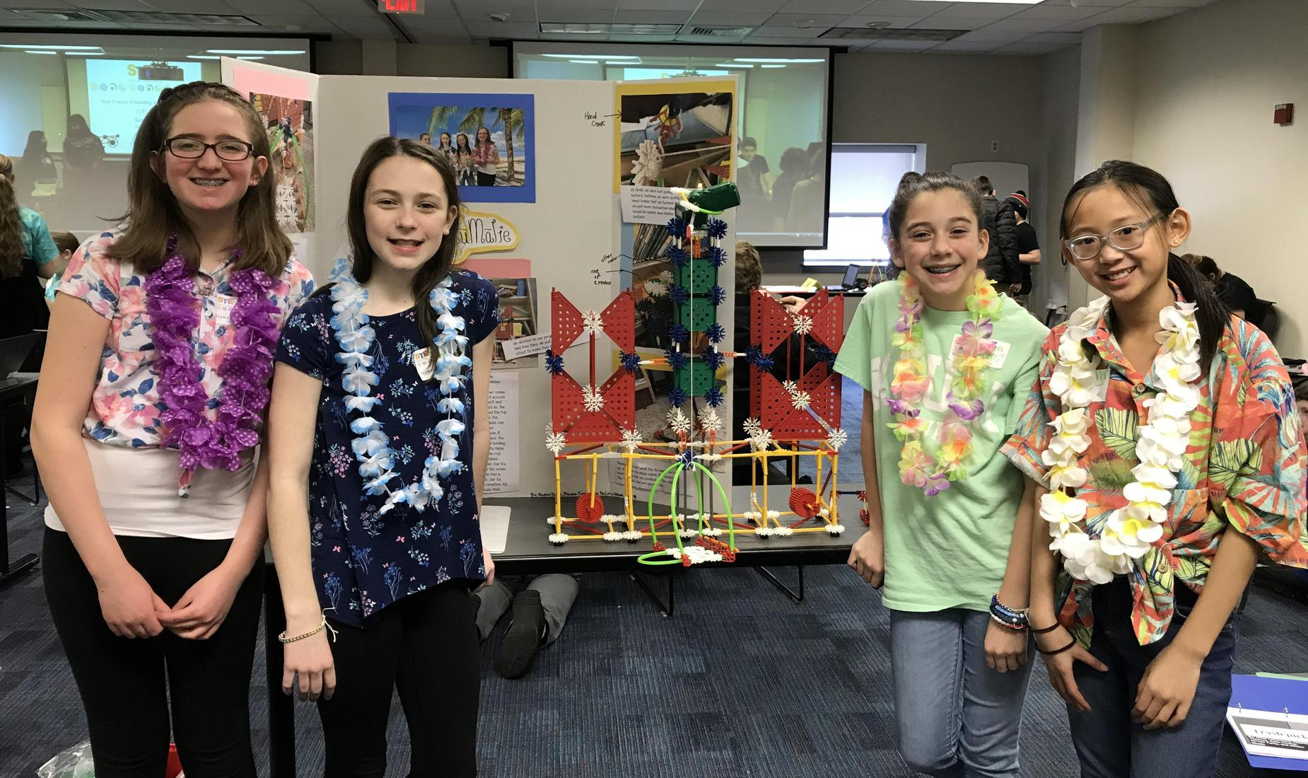 4 girls in colorful shirts with lays hanging on their neck showing their project from the K'Nex Challenge
