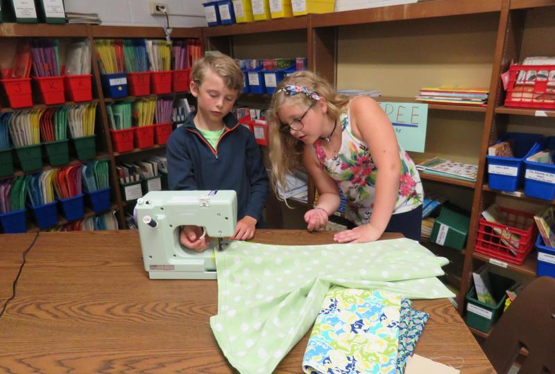 Lee third graders get a little help from a classmate in their sewing project.
