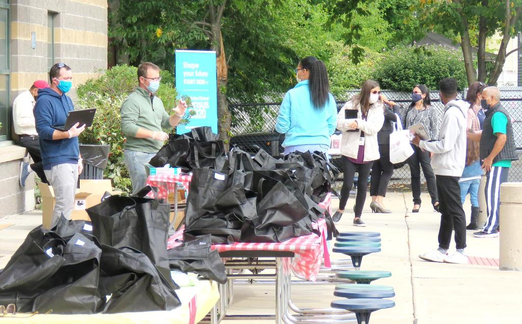 People gathered around tables filled with Chromebooks in black bags