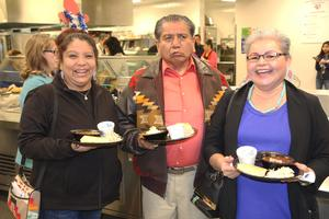 3 people who attended the bean feed posing with their meals