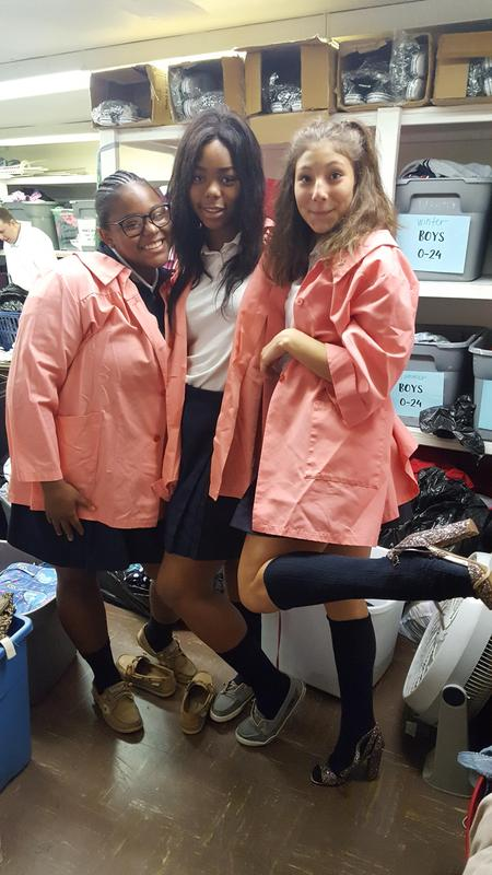 Three OLSH students volunteer at a thrift store during Mission & Heritage Week