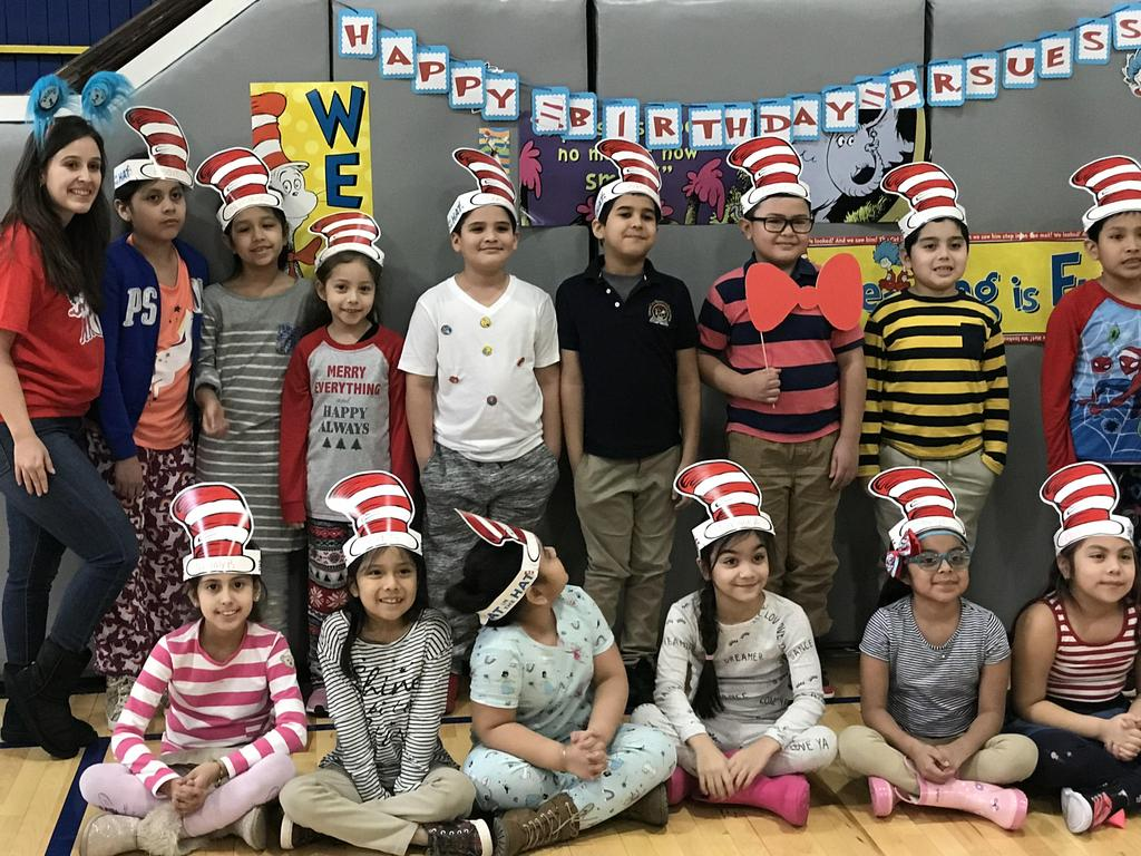 class with teacher posing in front of the Happy Birthday Dr. Seuss