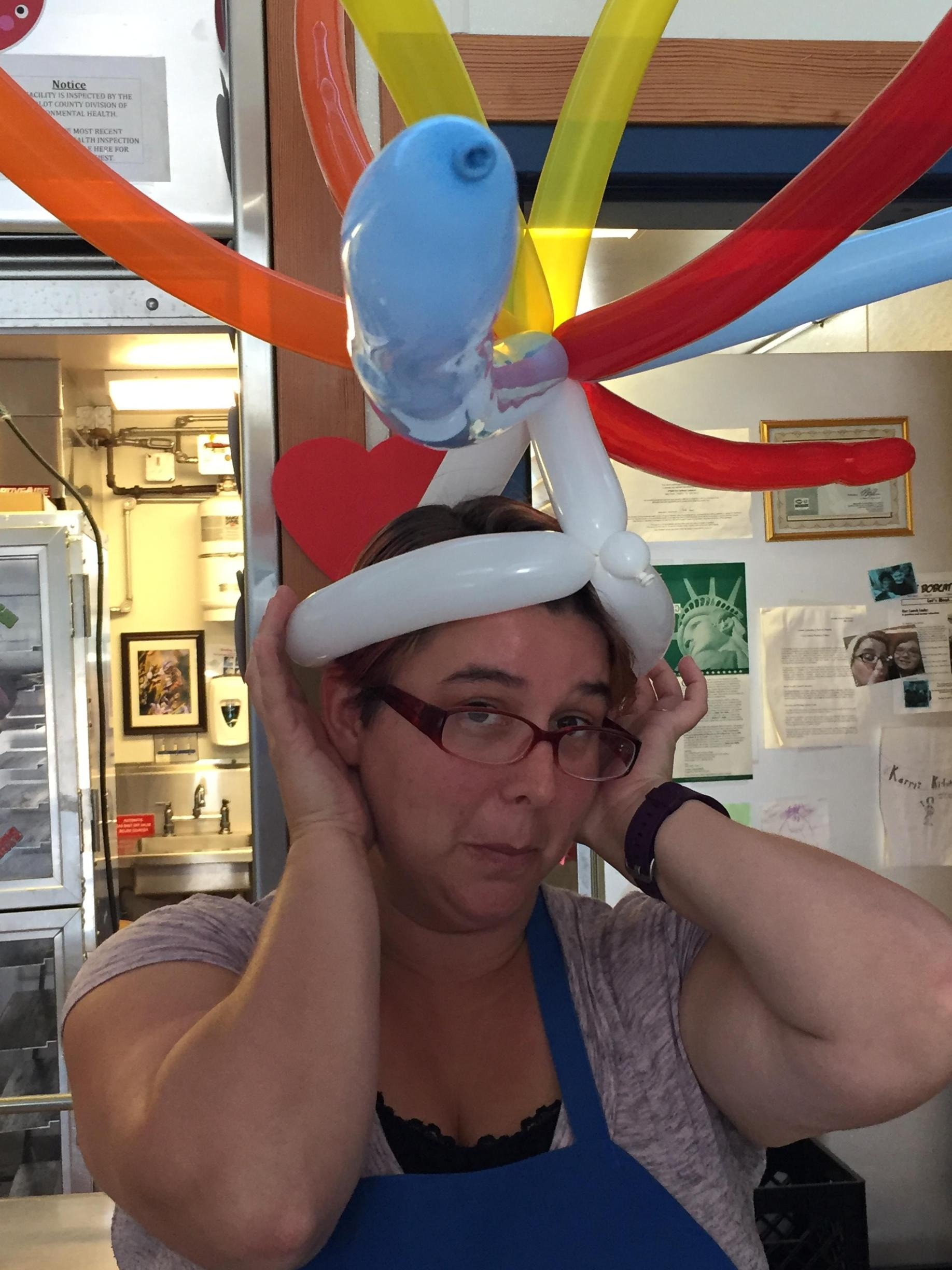 teacher wearing hat made from balloons