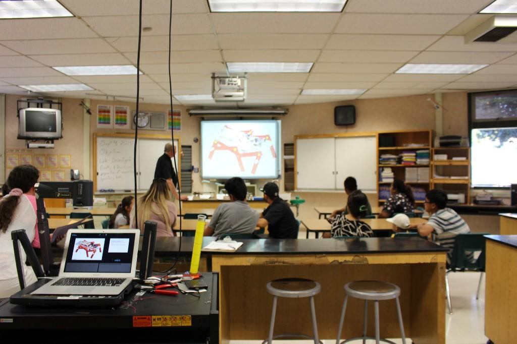 a teacher stands in front of class and shows a display on a projector screen while students sit at tables