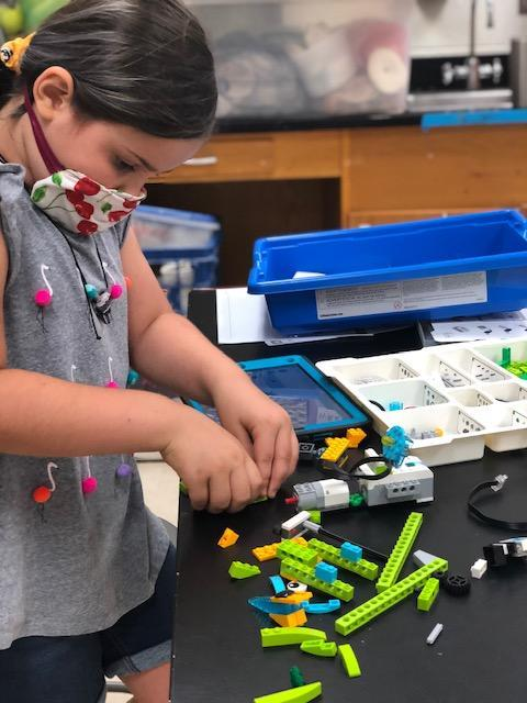 Student works on STEM project while wearing a mask.