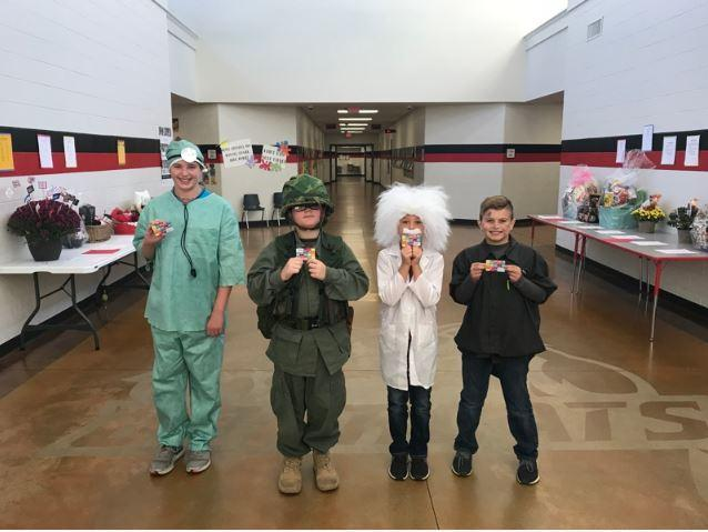 4 middle school students dressed as a doctor, soldier, scientist, artist