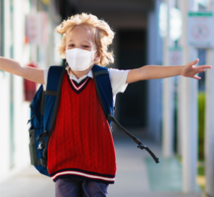 Student in mask running down halls with arms outspread in joy
