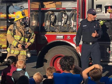 Firefighters showing students how they get ready to fight fire