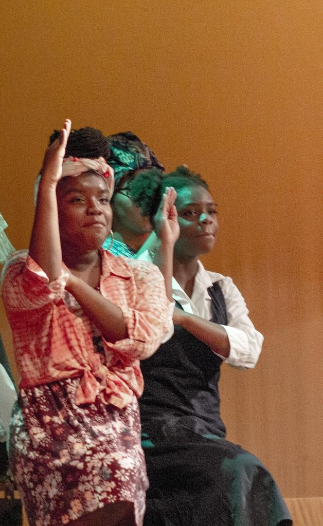 Two cast members make a saluting motion with their right hands