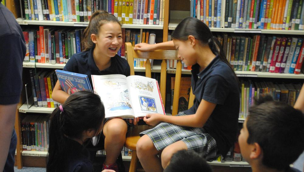 Older students in library reading to younger class.