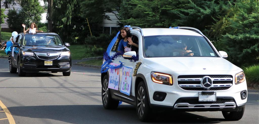 Photo of Washington 5th graders waving from cars during Grade 5 Clap Out Car Parade.