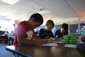 3 boys working in class.