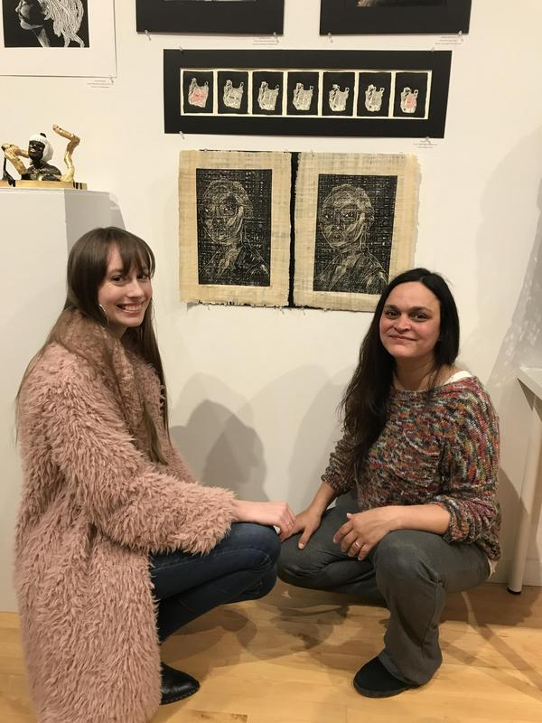 TEEN GIRL AND WOMAN CROUCHING NEXT TO BLACK AND WHITE DRAWINGS