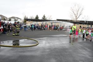 Fire department spraying water over students