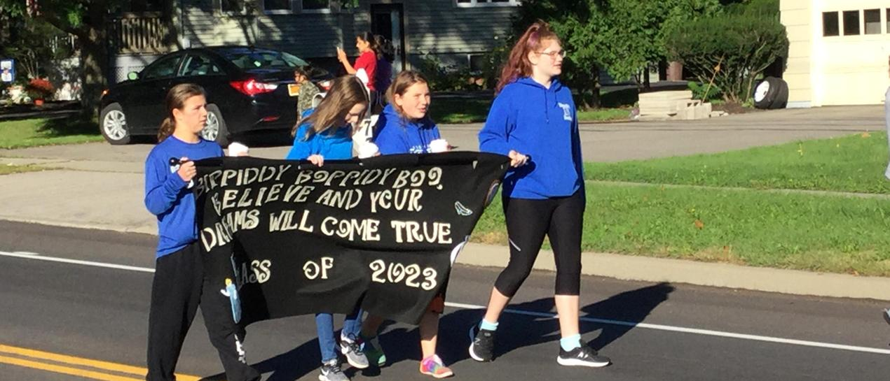 8th graders carrying a banner