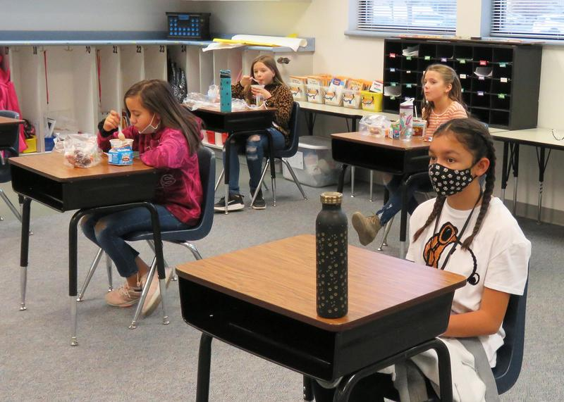 Girls eat their breakfast in a modified classroom where only half the children attend at a time.