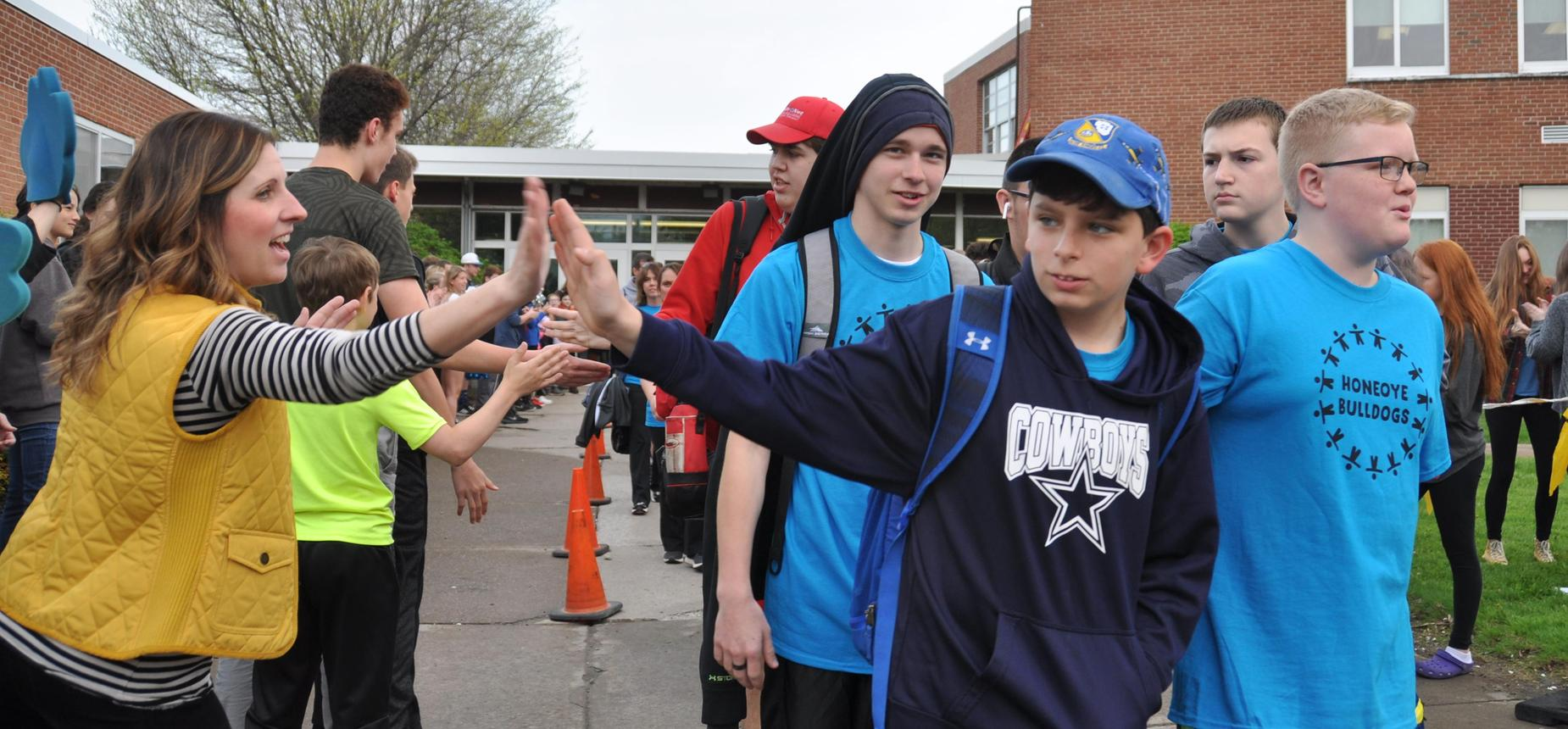 Students and staff cheering on our CORAL group as they head off to the Special Olympics