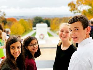 four students preparing for the wreath laying ceremony at Arlington National Cemetery.