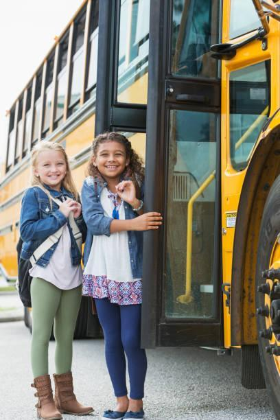 two multiethnic schoolgirls outside a school bus picture