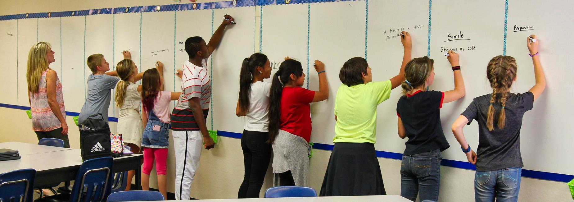 Students writing on a white board