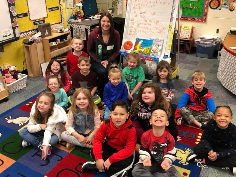 students and teacher pose together on their classroom rug