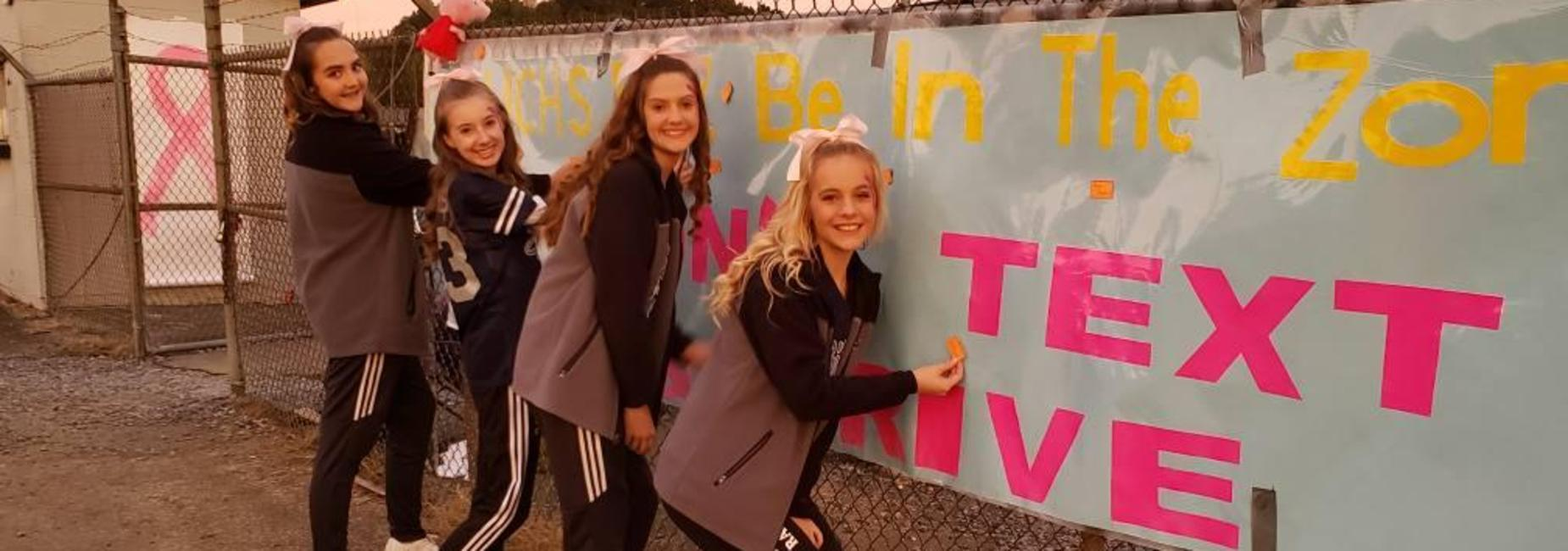 Cheerleaders sign the pledge to not text and drive.