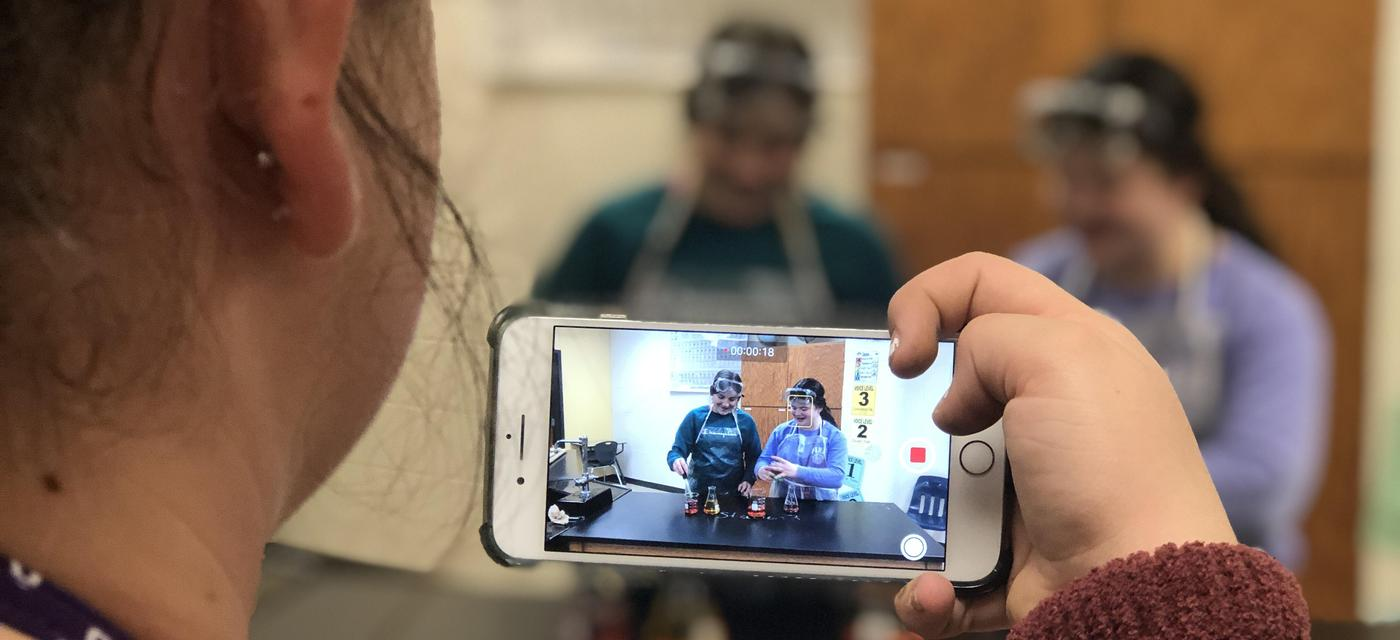 girl using camera phone to record 2 other girls in protective eye wear and aprons work with beakers of fluid
