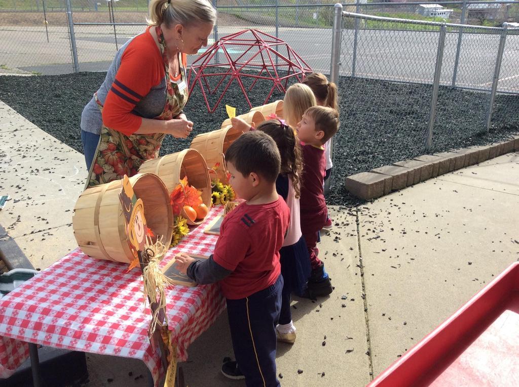 a teacher, children and baskets of vegetables