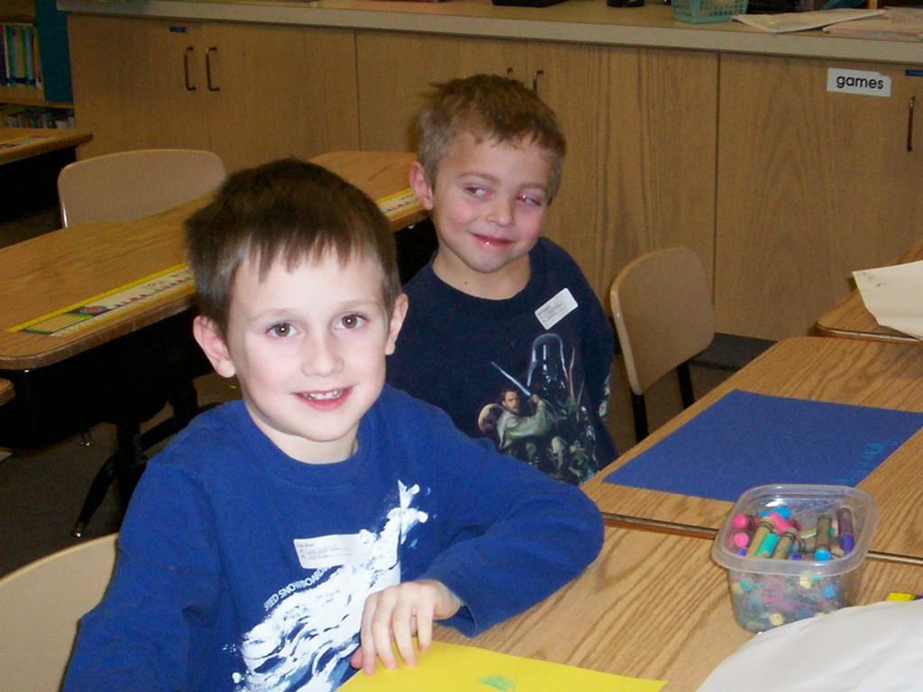 two boys smile for camera while coloring