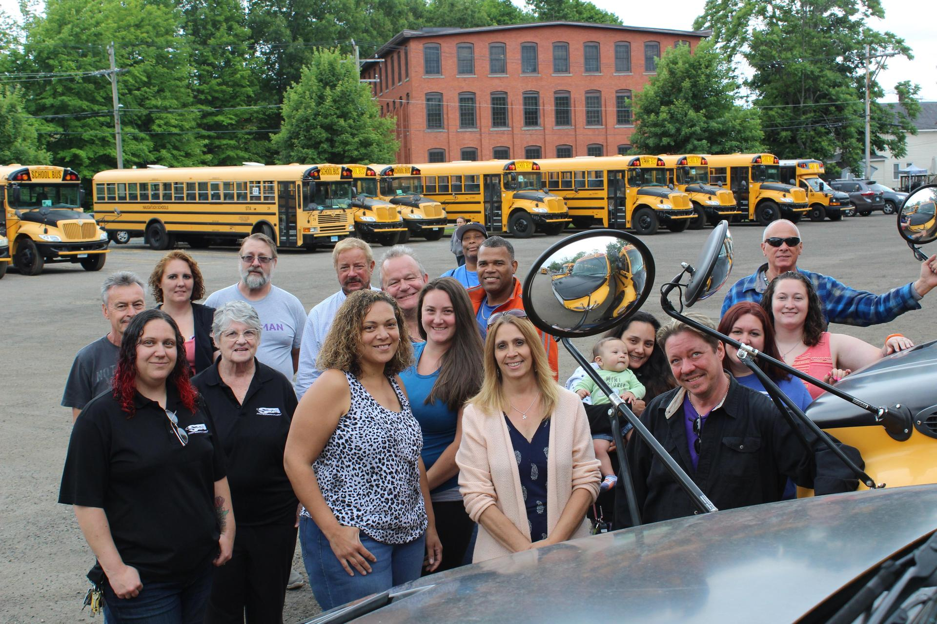 School bus drivers pose in front of bus