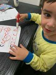 little boy in pj's make the c letter