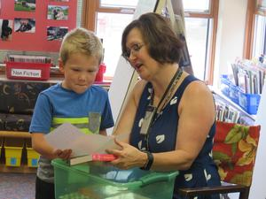 Kindergarten student David Dettmann anxiously listens as Ms. Young reads the note that came with his book.