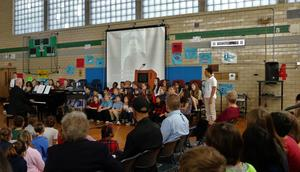 The Edison 8th Grade Chorus sings as a slideshow presentation honoring relatives of students and staff who served in the armed forces.