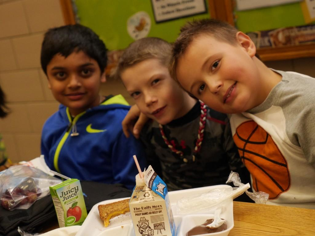 students pose for camera in lunchroom
