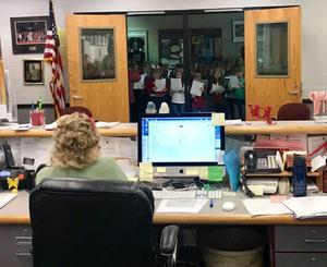 Second graders singing Christmas carols to GHS secretary