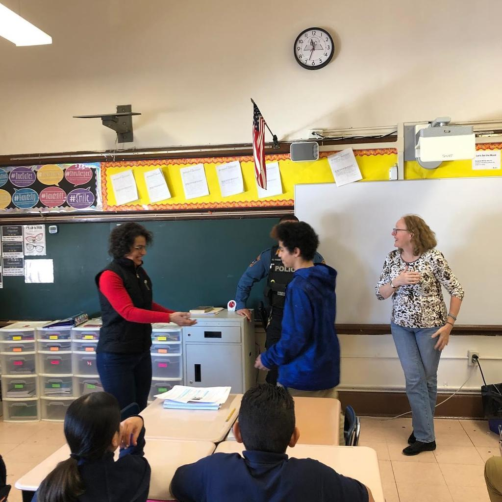 Mrs. Del Gaudio handing over a coin to a boy in front of her class