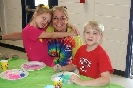 Mrs. Cavenaugh is painting rocks with her children.