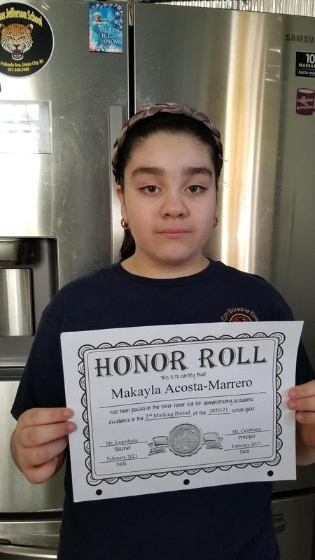 Makayla M. holding honor roll certificate