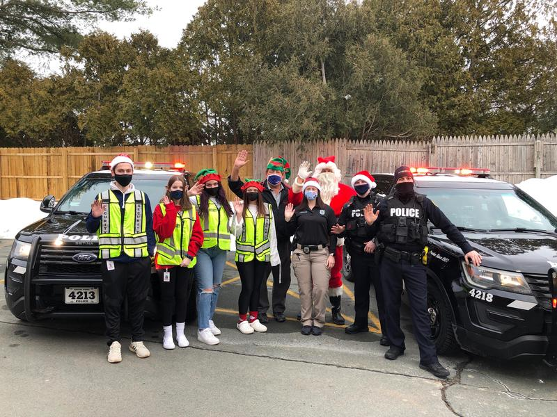 students with patrol officers loading gifts into car