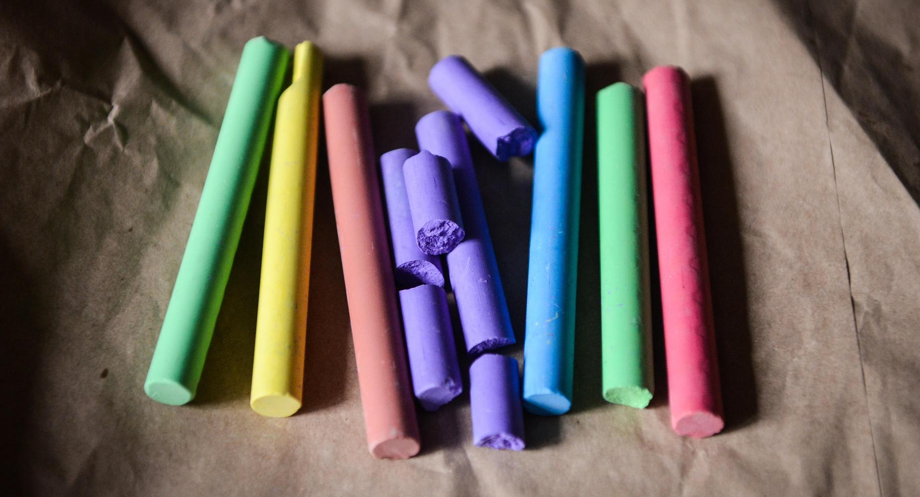 Colorful chalk is arranged in vertical lines on a paper bag