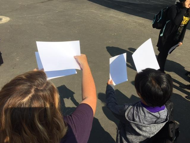 a teacher and students using paper and a pinhole to focus light of eclipse on a paper