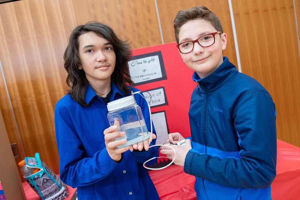 Two students hold the device they made for the science fair