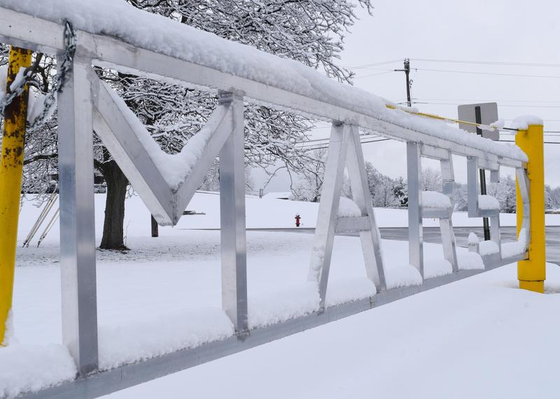 Snow on a parking lot gate with the word
