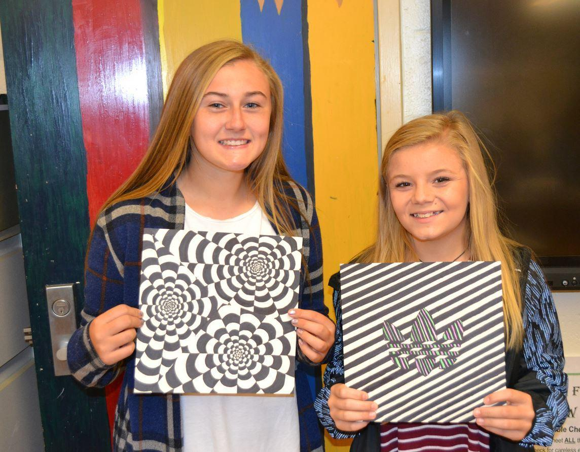 Students holding their artwork.