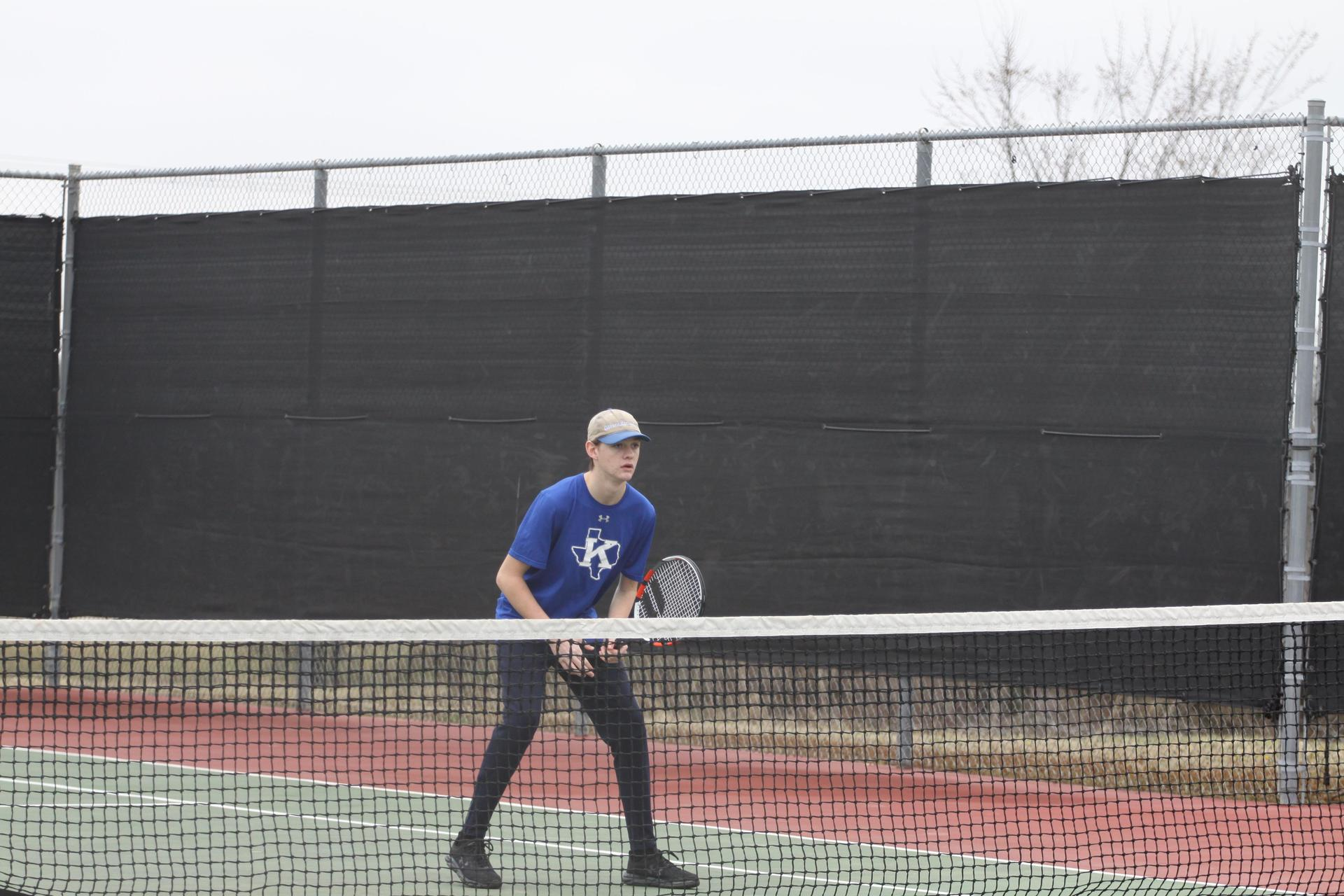 a tennis players stands ready with racket in hand behind the net