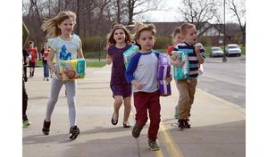 Primary Center students running with packages of diapers.
