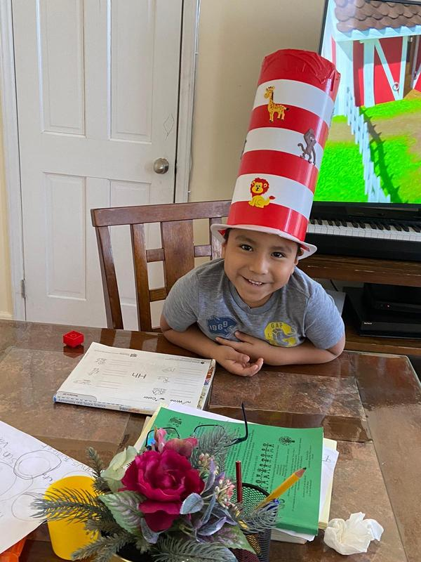 Saulo sitting at table in cat in the hat hat