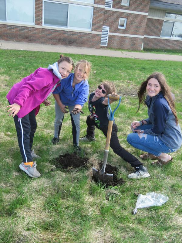 Page studentts plant seedlings out near their playground with TKHS student Lauren Myers.
