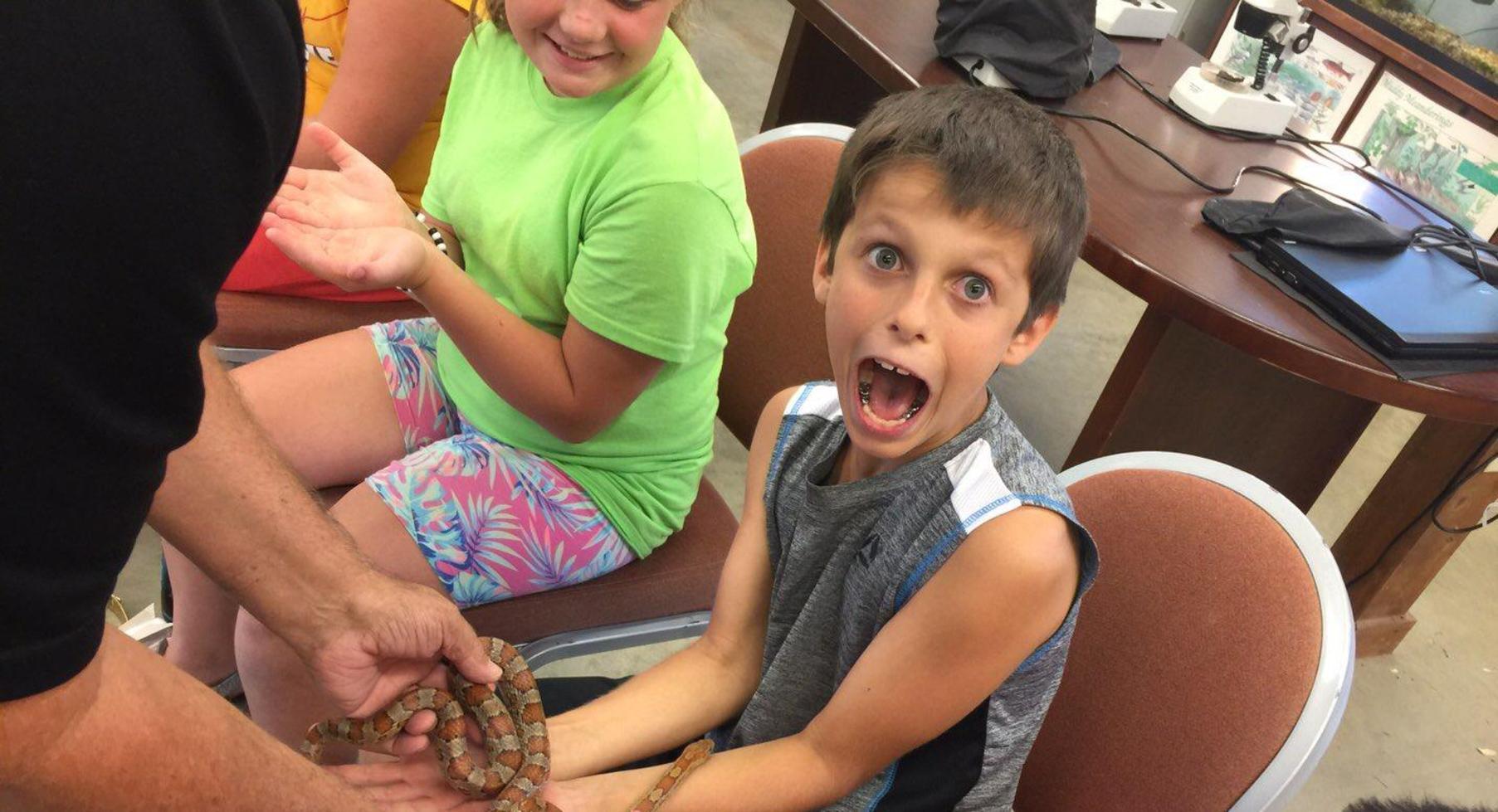 Student holding snake.